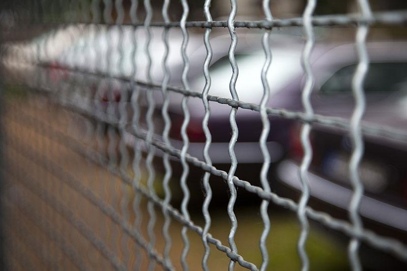 Blick auf die 7er-BMWs aus dem vergitterten Unterstand mit Grillplatz heraus