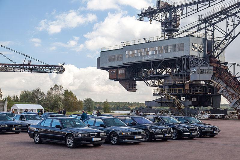 Gruppenfoto mit den teilnehmenden 7er-BMWs in der Arena der Ferropolis, im Hintergrund der Mad Max Eimerkettenbagger