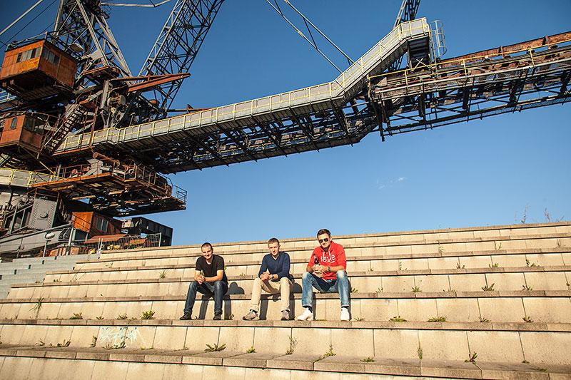 Teilnehmer sitzen unter dem Gemini Absetzer in der Ferropolis, mit Roman ('Godmod') und Peter ('Sachsen-7er')