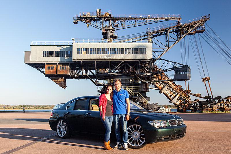 Chris ('750li') mit Freundin Natalie und seinem BMW 750Li (E66) vor dem Mad Max Eimerkettenbagger