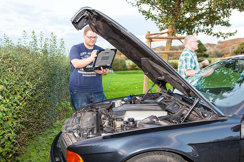 Sebastian ('Baschti', links) mit Diagnose-Laptop und Frank ('Festus03') am BMW 740iA (E38) von Frank
