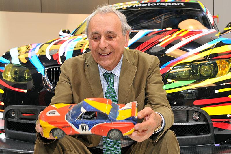 Hervé Poulain, Begründer der Art Car Collection, vor dem 17. BMW Art Car, hält eine Miniatur des 1. BMW Art Cars von Alexander Calder in seinen Händen