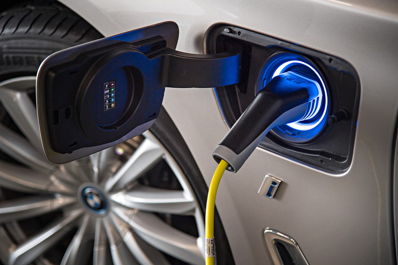 BMW 740Le xDrive iPerformance, als Hybrid erkennbar u. a. durch eine Ladebuchse vorne, darunter i Schriftzug, und blauer Radnabenabdeckung.