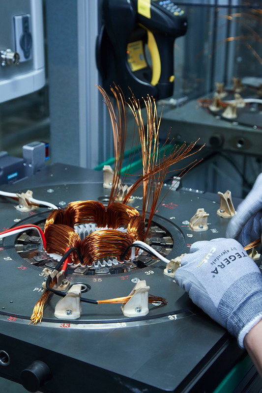 Die Kupferspulen werden teils per Hand am Stator befestigt.