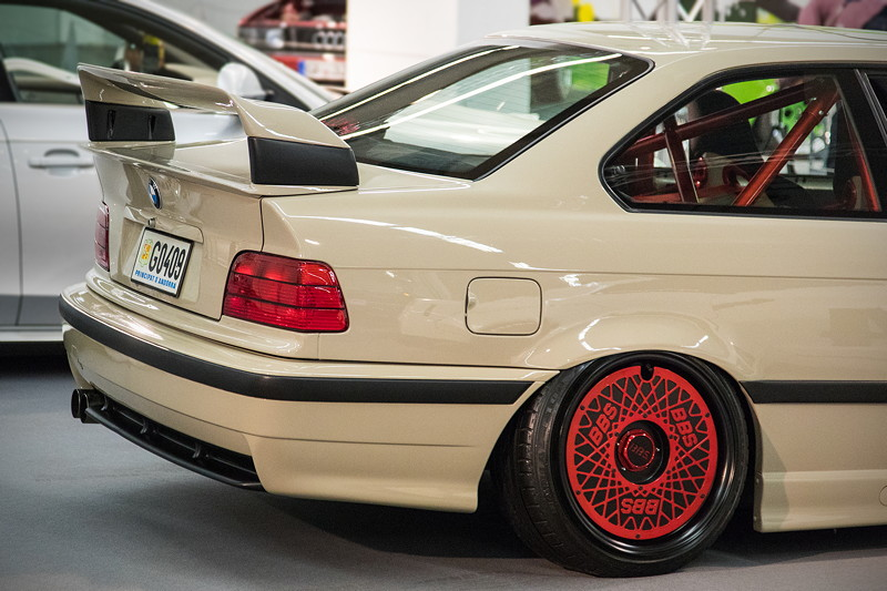 BMW 320i (E36) mit großem Heckspoiler.