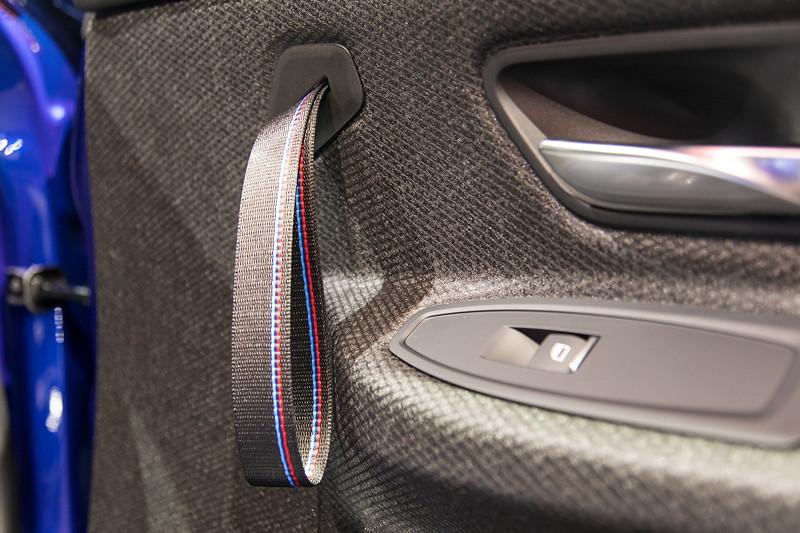 BMW M4 CS, Innenraum mit Türverkleidung aus Naturfaser und Handschlaufe mit M Streifen