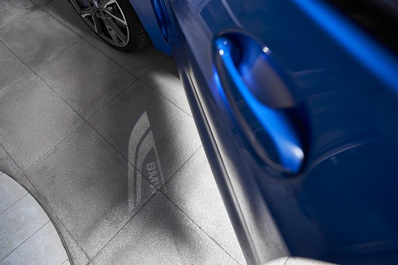 BMW M135i xDrive in Misanoblau metallic, Vorfeld-Beleuchtung mit BMW Schriftzug