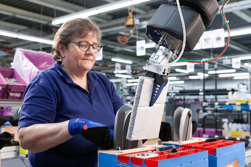 Technik unterstützt Mensch: Ohne Sicherheitszaun bewegen sich die Roboter direkt neben den Menschen und übernehmen beispielsweise monotone Arbeitsschritte.