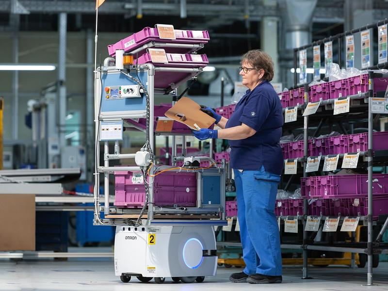 Eine Mitarbeiterin bestückt das autonome Transportsystem, das ohne weiteres Zutun seinen Weg durch die Halle zum Arbeitsplatz findet, an dem das Material benötigt wird.
